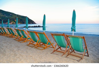 summer scene with warm colorful sunset on empty beach with closed green umbrellas and chairs in Versilia, Tuscany, Italy