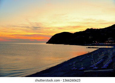 summer scene with warm colorful sunset on empty beach with closed blue umbrellas and chairs in Versilia, Tuscany, Italy