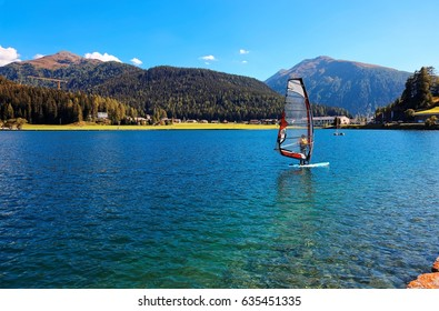 Summer scenery of Lake Davos on a bright sunny day with windsurfers poising sailboards on the turquoise water under blue clear sky & majestic alpine mountains in background, in Graubunden, Switzerland