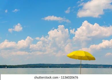 summer scenery at lake starnberg. view to the lake, yellow beach umbrella and blue sky with clouds and copy space.