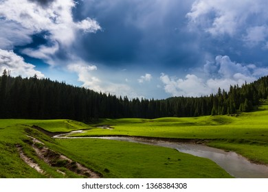 Summer scenery in the mountains, with beautiful green pasture, river and storm clouds