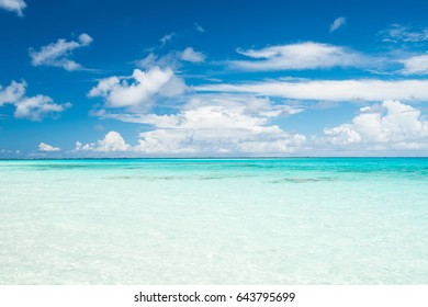 Summer scenic view on the beach with turquoise sea water, blue sky and white clouds