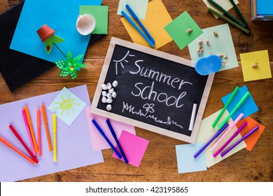 Summer school composition on a wooden table with a blackboard, chalk, colored papers and pens