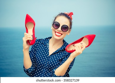 Summer at sea. Closeup portrait beautiful happy free young pretty woman excited stylish fashion girl looking at you camera smiling holding red shoes isolated seascape ocean background outdoor vacation