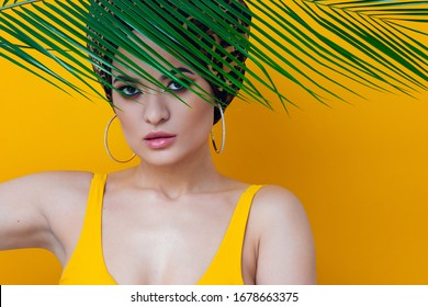Summer sea and the hot weather, the beach trend. A young beautiful multi-ethnic woman in a leopard turban and yellow bathing suit looks out from behind a palm branch, yellow mango background