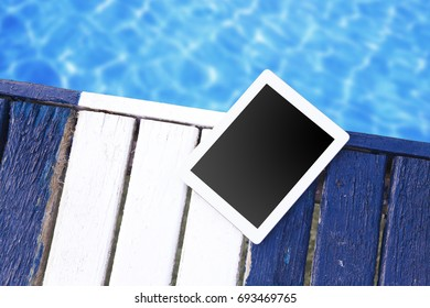 Summer sea vacation mock-up background. Blank screen tablet pc on striped blue wooden deck. Top view.