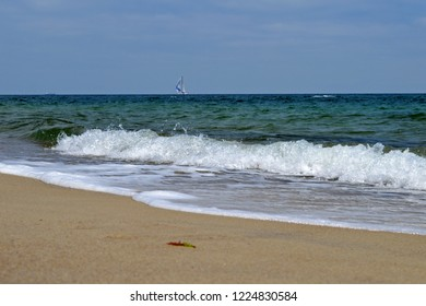Summer sea view with sandy beach, waves and yacht