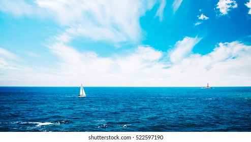 Summer Seascape with Clear Blue Water, Sailing Yacht and Lighthouse on Horizont. Copy Space Background. Toned and Filtered Photo. Panoramic Image Can Be Used as Web Banner or Wide Site Header.