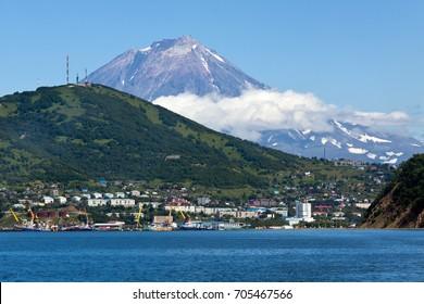 Summer seascape of Kamchatka Peninsula: view of Petropavlovsk-Kamchatsky City, Avacha Bay (Pacific Ocean) and active Koryak Volcano (Koryaksky Volcano). Eurasia, Russian Far East, Kamchatka Region.