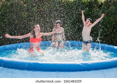 Summer season concept background.  Three happy school children friends - one boy, two girls - have fun making water splashes in inflatable garden swimming pool, refreshing themselves in hot weather