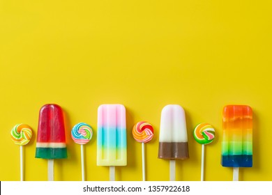 Summer season concept. Colorful ice creams and lollipops on yellow background with free copy space.