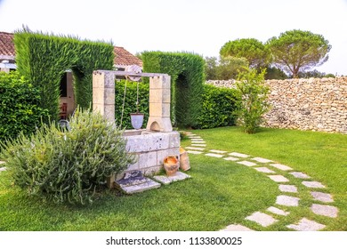 Summer season in Italy. Desing water well in an elegant garden.