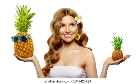 Summer selection. The girl chooses between large and small pineapple. Concept of travel. Beautiful female model with tropical fruits in her hands