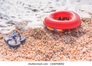 Summer shells beach with children's flip flops mask and donut for swimming in the sea.