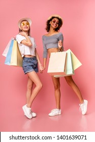 Summer shopping. Diverse stylish girls shoppers posing with colorful shopping bags, pink studio background