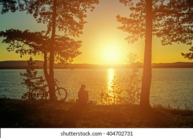 Summer silhouette landscape - unidentified tourist girl with bicycle at the edge of the cliff looking the sun setting behind the mountains on  Irtyash Lake in Southern Urals, Russia