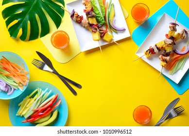 Summer simple recipe for grilling, hawaiian chicken kabobs served with freshly diced vegetables and some orange drink in glasses, view from above template with a space for a text
