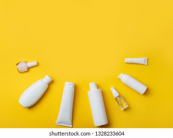 summer skin care cosmetics on yellow background. White bottles of woman cosmetics on yellow. Summer holidays or vacation. Preparation for summer care. Sunscreen protection  products