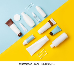 summer skin care cosmetics on yellow and blue background. White bottles of woman cosmetics on yellow. Summer holidays or vacation. Preparation for summer care. Sunscreen protection  products