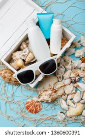 summer skin care cosmetics, panama and sunglasses on blue background.  bottles of woman cosmetics on seashells. Summer holidays or vacation. Preparation for summer care. Sunscreen protection products