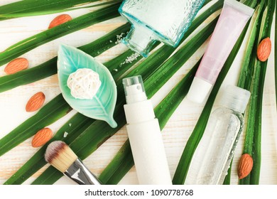 Summer skincare natural cosmetic products viewed above on fresh green palm leaf background. Facial tonic and cream, sea salt, lip balm. Home spa.