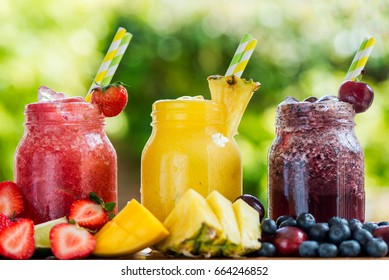 Summer Slushies from Blueberries, Cherries, Lemon, Mango, Strawberries, Lime, Pineapple and Ice with Ingredients nearby, on natural background