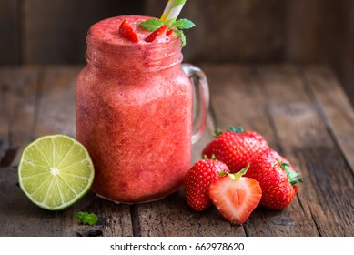 Summer Slushy from Strawberries, Lime and Ice with some ingredients nearby on dark rustic background
