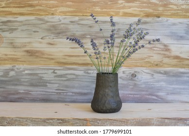 Summer smell with lavender in unique handmade vase of black pottery with log house wall on background