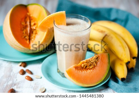 Summer smoothie: fresh melon, banana and almond milk. Healthy light food, vitamins and energy source. Served on mint blue plates. Contrast bright colors, vacations mode on