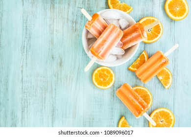 Summer snack of orange popsicles in a bowl with ice on wooden background