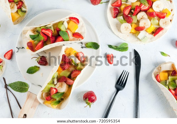 Summer snacks. Food for a party. Fruit tacos with strawberries, mangoes, bananas, chocolate, mint. On a light blue concrete table. Copy space top view