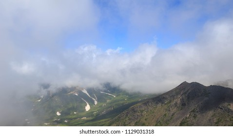 Summer snow visible below clouds on Hokkaido mountain range