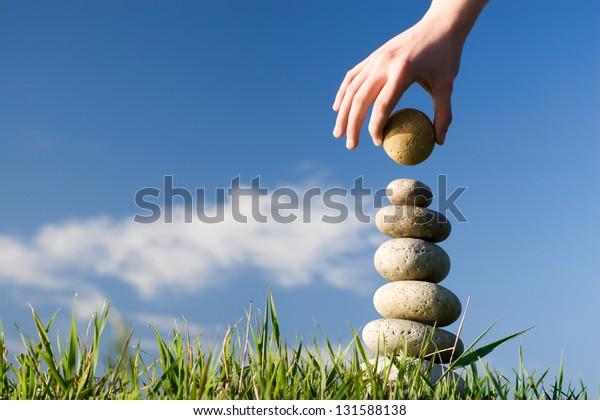 Sommer. Jemand baut Gleichgewicht auf einem Gras.
