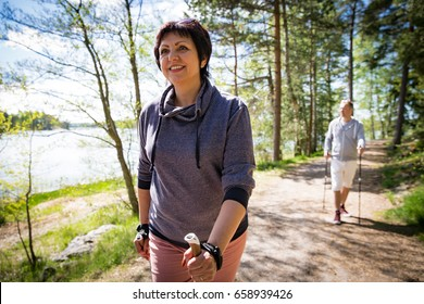 Summer sport in Finland - nordic walking. Man and mature woman hiking in green sunny forest. Active people outdoors. Scenic peaceful Finnish summer landscape.