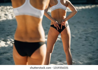 summer, sport, gesture, holidays and people concept - close up of woman buttocks and hands showing beach volleyball hand sign meaning angle attack block