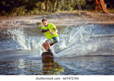 Summer sport wakeboarding. The sportsman slides on the lake's water on the board.