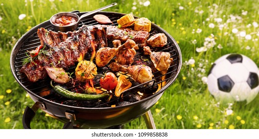 Summer or spring barbecue outdoors in a meadow with dandelions and a soccer ball with assorted vegetables, spicy spare ribs and chicken legs grilling on the fire