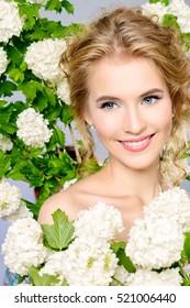 Summer, spring inspiration. Smiling young woman with natural make-up and beautiful curly hair posing with white flowers. Beauty, fashion, cosmetics.