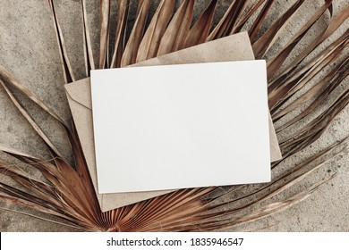 Summer stationery still life. Closeup of blank card mock-up and craft envelope on dry palm leaf. Grunge beige concrete background. Flat lay, top view, tropical vacation concept. Moody boho design.