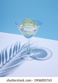 Summer stationery still life scene made with glass, dried lemon, drink, and trend palm shadow on blue pastel background. Summer vacation refreshment concept. Long shadow and refraction pattern. - Shutterstock ID 1906005763