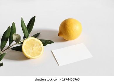 Summer stationery still life scene. Cut lemon fruit and olive tree branch nad leaves  in sunlight. Blank business card mockup isolated on white table background. Branding concept, Mediterranean design - Shutterstock ID 1974455963