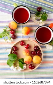 Summer still life with berry tea, ripe apricots, juicy cherries and apple blossoms. Selective focus, top view