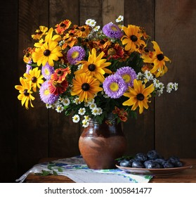 Summer still life with a bouquet of garden flowers in a clay jug and blue plums in a country style.