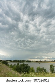 A summer storm sweeps in with stunning wavy clouds over a Midwestern pond.