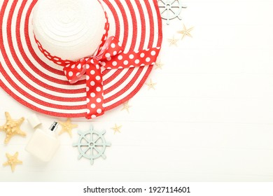 Summer straw hat with starfishes, perfume bottle and decorative steering wheel on white wooden table