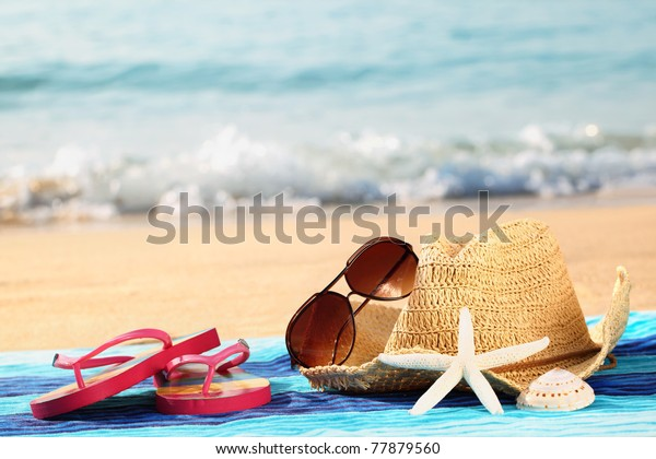 Summer straw hat with towel,sunglasses and flip flops on sandy beach