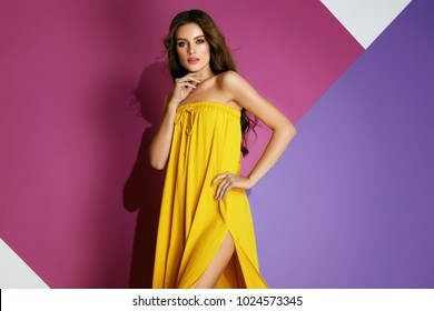 Summer Style. Beautiful Female Model In Colorful Dress. Gorgeous Sexy Woman In Bright Trendy Yellow Clothes With Long Hair, Glamour Makeup On Pink Violet Background. Fashion And Beauty. High Quality