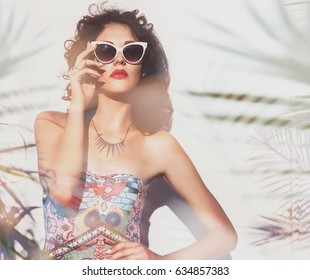 Summer style portrait of young attractive woman wearing sunglasses. Tropical holiday fashion beauty concept