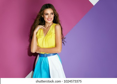 Summer Style. Woman In Colorful Stylish Dress. Beautiful Happy Smiling Female Model With Beauty Makeup, Long Hairstyle Wearing Trendy Bright Summer Or Spring Clothes On Violet Background. High Quality
