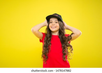 Summer sun protection cap. Girl long curly hair wear cap. Must have street style accessory trends. Modern fashion. Kids fashion. Cute child wear cap or snapback hat. Little girl wearing baseball cap.